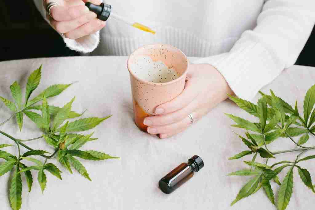 A woman drops CBD on a cup of coffe